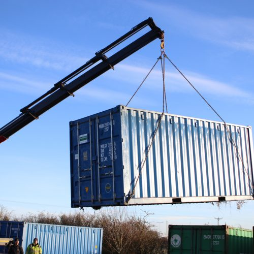 Container loading - 20ft new 'one trip' container being lifted from the bottom with a HIAB assisted vehicle.